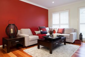This red accent wall is just too abrupt of a change from the adjacent white wall and is disconcerting to the eye, even though the owners have tied in the red in the throw and a couple of pillows. Red drapes and red in the rug would tie it together much better.